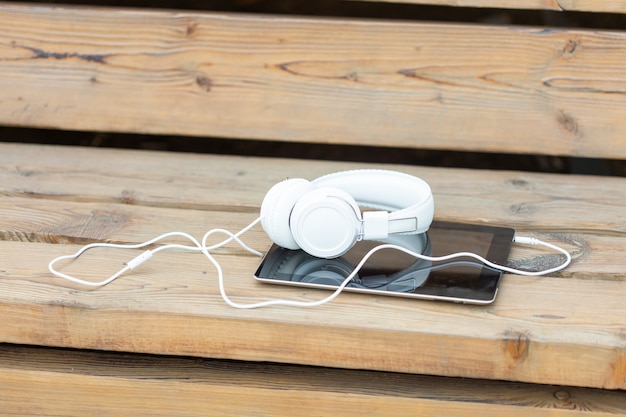 Auriculares y una tableta se encuentran en un banco de madera en el parque en una cálida noche de verano. concepto de caminar en el parque de la ciudad de verano y escuchar música y estudiar.
