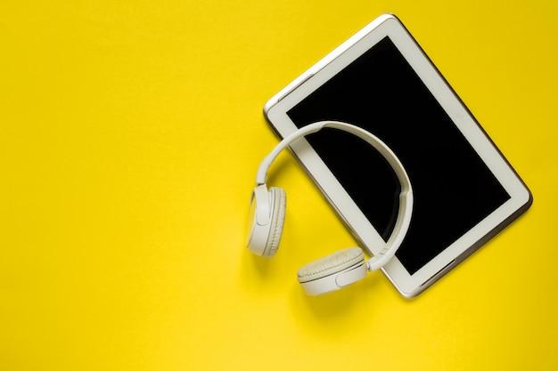 Los auriculares y la tableta modernos blancos en el plano amarillo tendido del backgound ponen el espacio de la visión superior para el texto