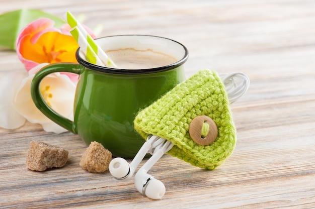 Auriculares y taza de café con tulipanes.
