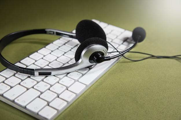 Auriculares en teclado blanco. concepto de servicio de soporte