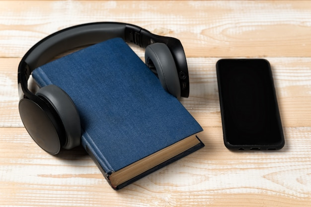 Auriculares, teléfono y libro. aprendizaje a través del concepto de audiolibro. fondo de madera