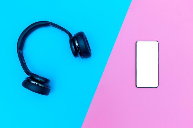 Los auriculares y teléfonos negros se colocan sobre un fondo azul y rosa