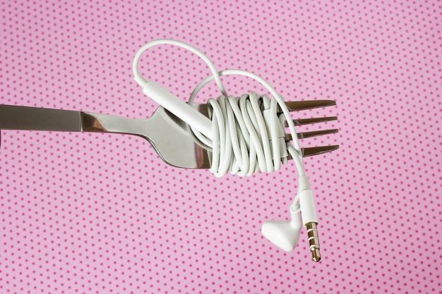 Auriculares y tenedor blancos sobre un fondo rosa con lunares, primer plano