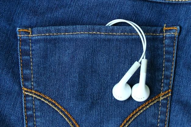 Auriculares en el tono vintage de color del bolsillo trasero de la mezclilla