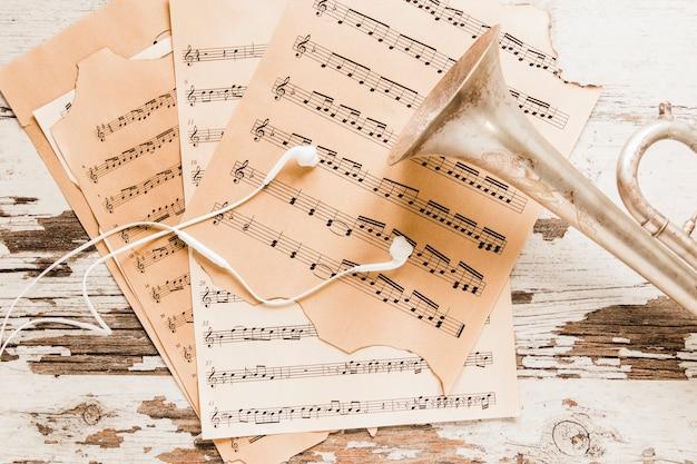 Auriculares y trompeta en partituras