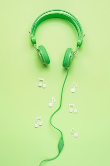 Auriculares verdes con notas musicales blancas