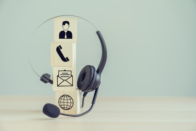 Auriculares voip y comunicación de iconos en el bloque de madera.