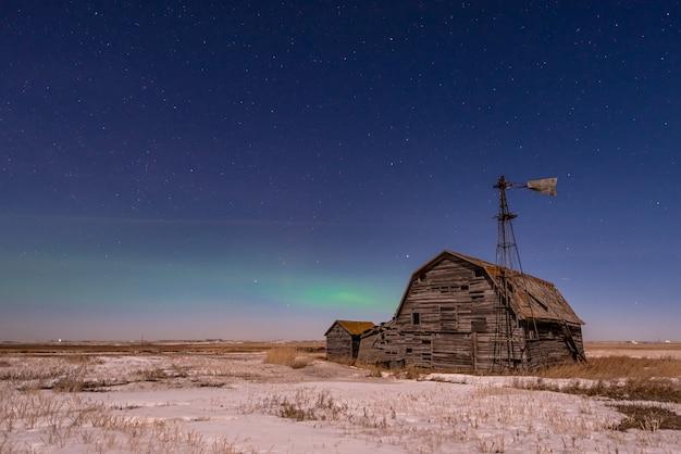 Aurora boreal sobre granero vintage, contenedores y molino de viento en saskatchewan, canadá