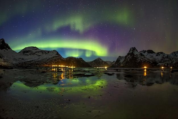Aurora boreal sobre la montaña reflejándose en un lago