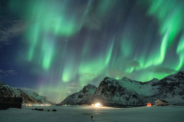 Aurora borealis, auroras boreales sobre montaña nevada y viajero caminando en invierno en las islas lofoten
