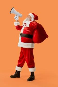 Auténtico papá noel con bolsa roja llena de regalos gritando en megáfono blanco