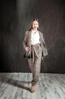 Auto confianza. mujer joven alegre avanzando mientras está en demostración de moda