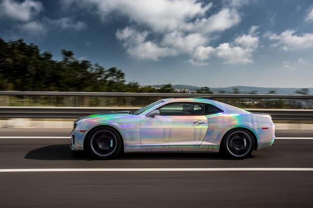 Auto deportivo blanco con autoajuste azul en la carretera