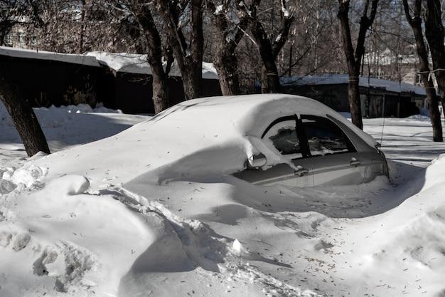 El auto plateado está en el estacionamiento en un gran banco de nieve. problemas climáticos