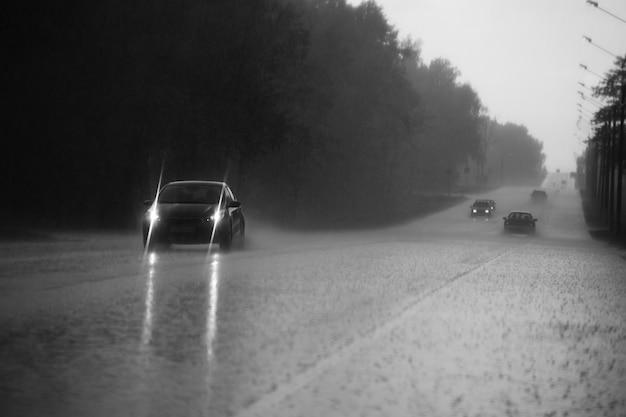 El auto sale a la carretera con aguacero. imagen desenfocada, borrosa