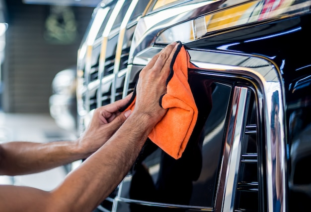 Auto servicio trabajador pulido coche con paño de microfibra.