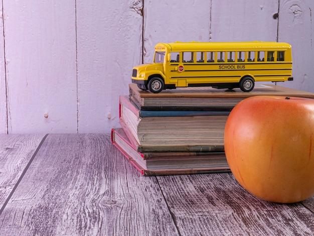 El autobús escolar en la mesa de madera para el concepto de educación