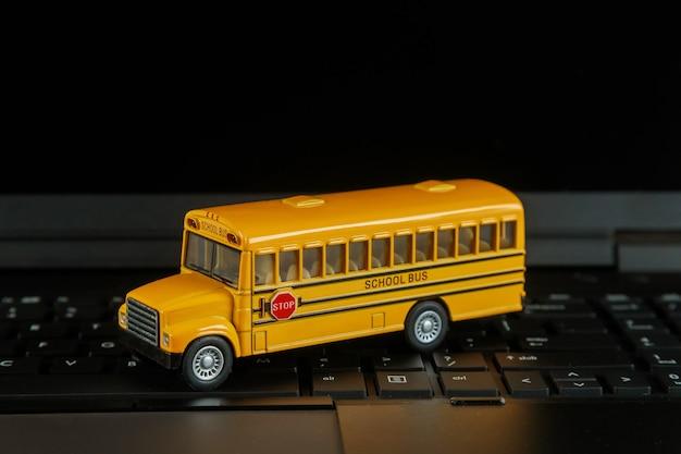 Autobús escolar en teclado de computadora de cerca con lección en línea de regreso a la escuela