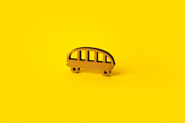 Autobús de juguete de madera sobre fondo amarillo, autobús de transporte público