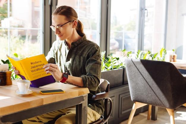 Autoeducación. buen hombre guapo leyendo un manual mientras estudia palabras en japonés