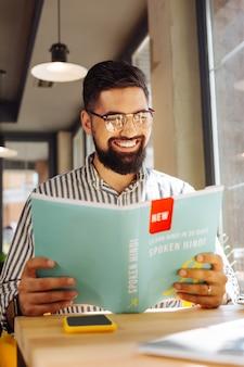 Autoestudio. hombre barbudo positivo sonriendo mientras estudia un nuevo idioma por sí mismo