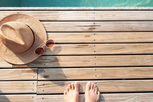 Autofoto de pies descalzos sobre suelo de madera con gorra y gafas de sol. concepto de verano