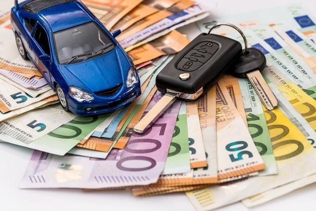 Automóvil de juguete y llaves reales en billetes en euros