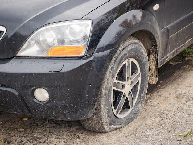 Un automóvil negro con una rueda delantera desinflada.