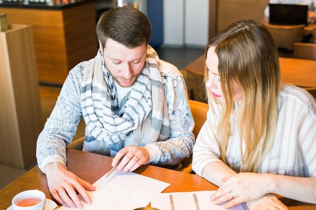 Autónomos hombre y mujer discutiendo ideas y tomando notas
