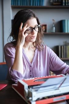 Autora madura pensativa en lentes pensando y mirando a otro lado