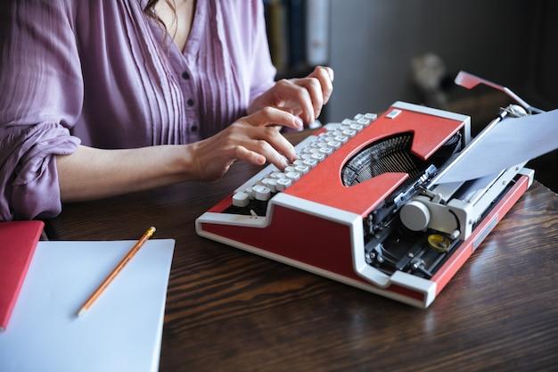 Autora sentada en la mesa y escribiendo en máquina de escribir en el interior