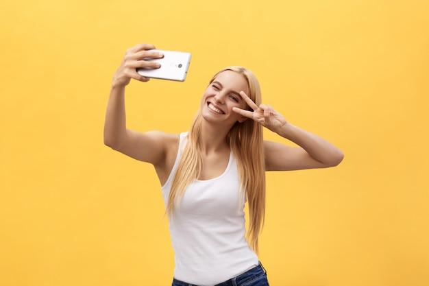 Autorretrato de una chica alegre encantadora que dispara autofotos en la cámara frontal que gesticula el símbolo de paz con signo en v
