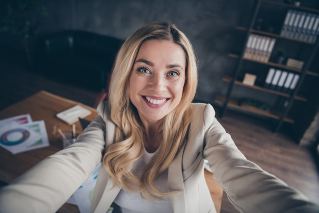 Autorretrato de dama de negocios alegre toothy radiante tomando selfie en su oficina