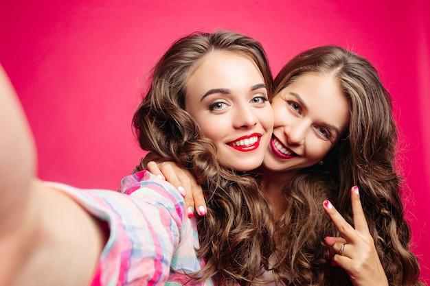 Autorretrato de hermosas chicas morenas en estudio rosa.