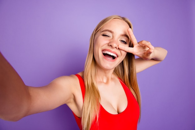 Autorretrato de rubia alegre mostrando v-sign