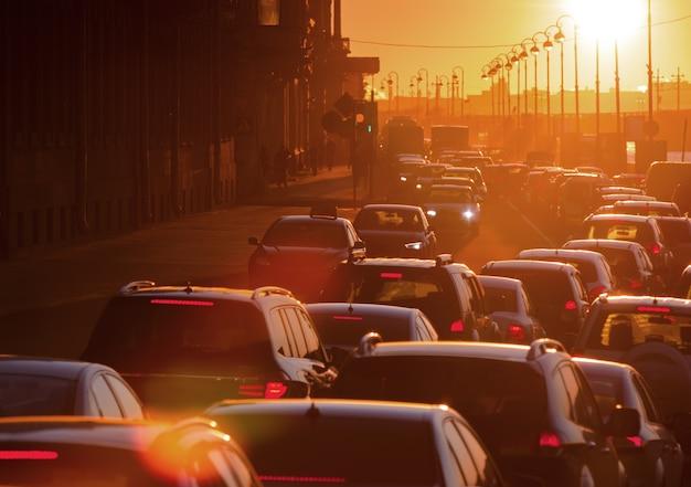 Los autos se encuentran en un embotellamiento durante una hermosa puesta de sol dorada en una gran ciudad.