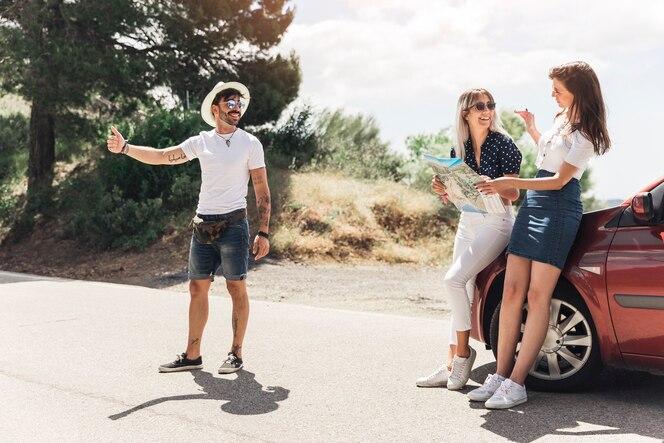 Autostopista masculino con sus dos amigas por la carretera durante el viaje de vacaciones