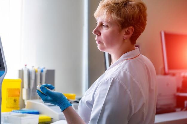 Auxiliares de laboratorio analizando muestra de sangre. asistencia en guantes. prevención. diagnóstico de neumonía. identificación de covid-19 y coronavirus. pandemia.