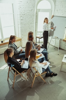 Avanzado. oradora femenina dando presentación en el salón del taller. centro de negocios. vista de ángulo alto de los participantes en la audiencia. evento de conferencia, formación. educación, diversidad, concepto inclusivo.
