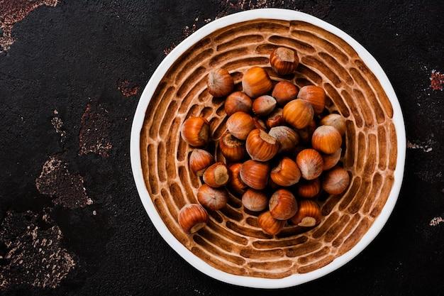 Avellanas crudas saludables en placa de cerámica sobre superficie de hormigón marrón