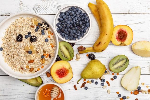 Avena con fruta y miel sobre una mesa de madera blanca