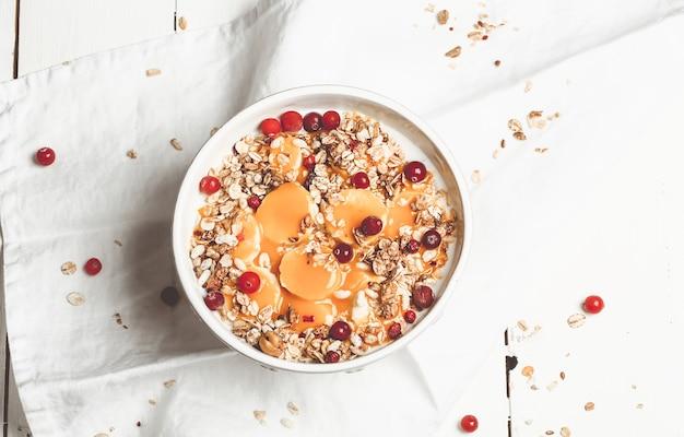 Avena con frutos rojos, plátano y mango. productos naturales de salud para la alimentación de la mañana. desayuno saludable