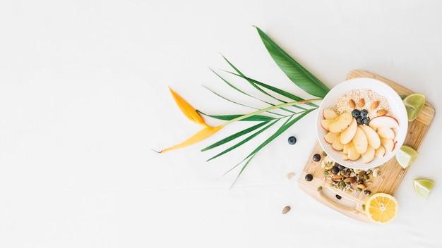 Avena y frutos secos con flor de ave del paraíso sobre fondo blanco