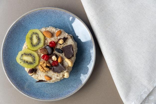 Avena con nueces y chocolate en una placa azul. nutrición apropiada.