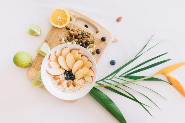 Avena saludable y frutos secos en la tabla de cortar con flor