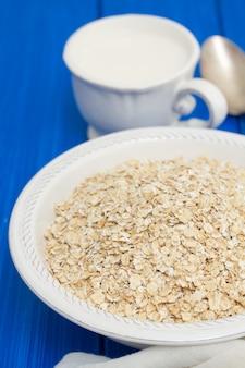 Avena en un tazón blanco y una taza de leche en la superficie de madera