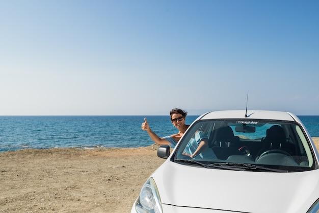 Hacia la aventura! chica relajante y disfrutando de viaje por carretera. la muchacha feliz monta en la puesta del sol en el coche blanco. concepto de alquiler de coches. mujer joven, conducir un coche, en la playa