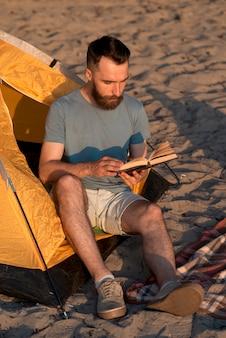 Aventurero sentado y leyendo un libro.