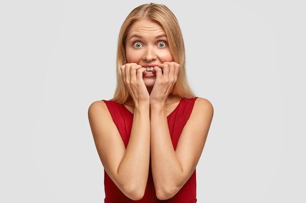 Avergonzada mujer rubia se muerde las uñas, mira sorprendentemente y con expresión preocupada