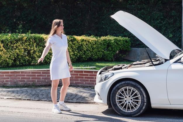 Avería de coche una mujer hermosa vestida de blanco ha roto su coche y está tratando de encontrar ayuda en el ...